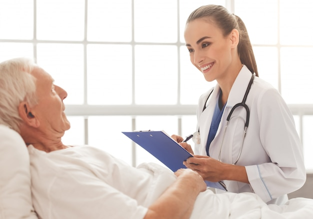 Doctor in white medical coat is listening to her old patient