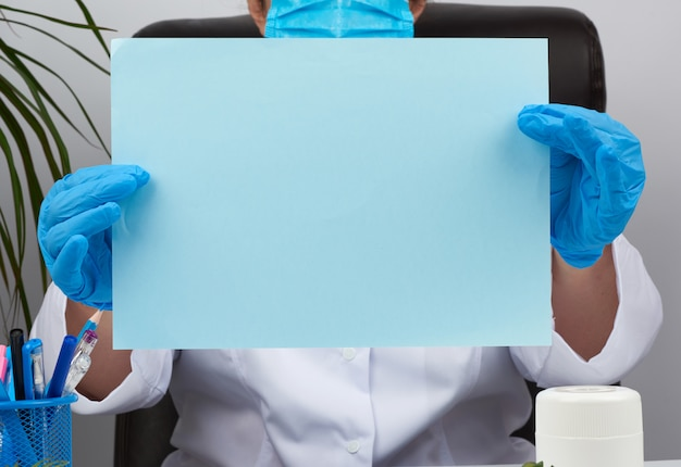 Doctor in a white medical coat is sitting at a table in a brown leather chair and holding a empty blue sheet of paper in his hands