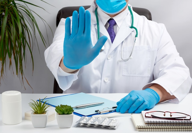 Doctor in a white medical coat sits at a table in a brown leather chair and shows with his palm a gesture of stop