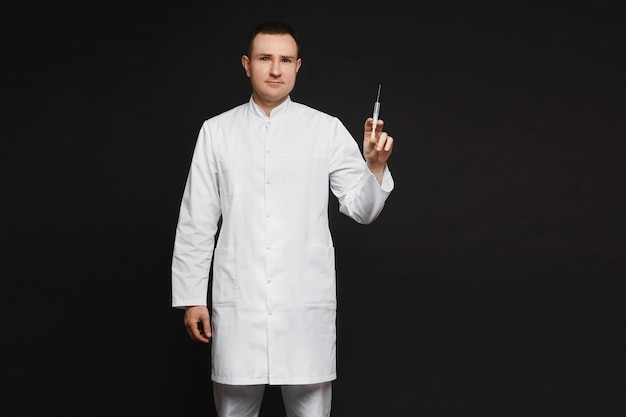 Doctor in white medical gown holding medical syringe for injection, isolated on black background.