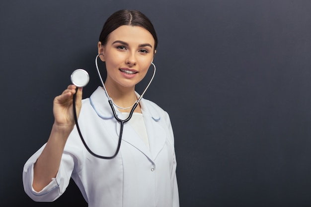Doctor in white medical gown is holding a stethoscope. copyspace