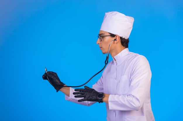 Doctor in white medical uniform checking with stethoscope on blue.