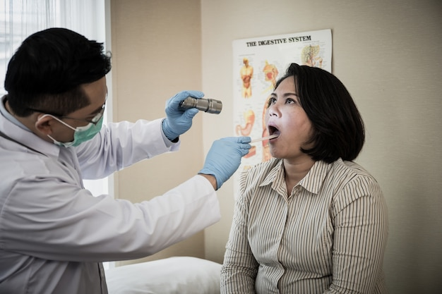 Doctor in white uniform gown checkup patient's mouth with flashlight: physician check up.