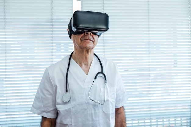 Doctor at the window of a hospital, using virtual reality glasses for medical purposes, looking to the right