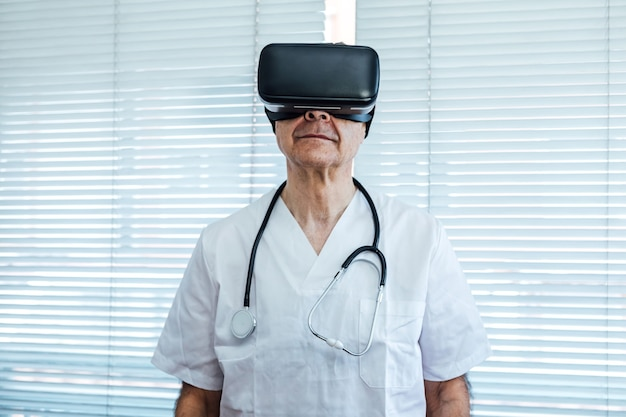 Doctor at the window of a hospital, using virtual reality glasses for medical purposes, looking up