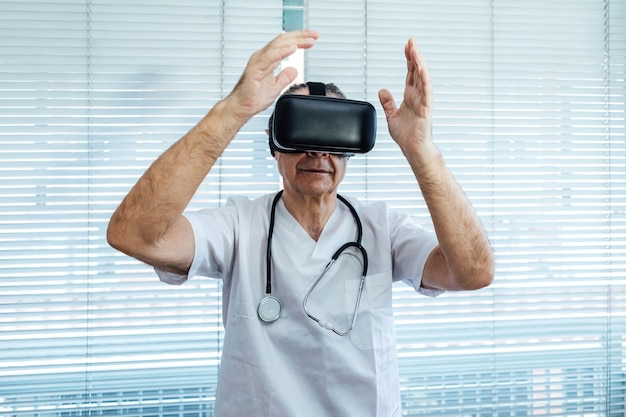 Doctor at the window of a hospital, using virtual reality glasses for medical purposes, touching something virtual with his hands