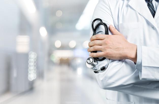 Врач с черным стетоскопом на фоне больницы