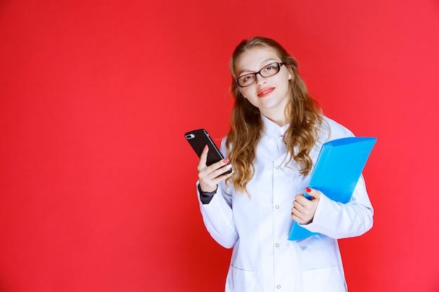 青いフォルダーと眼鏡を持った医者が彼女の電話をチェックしています。