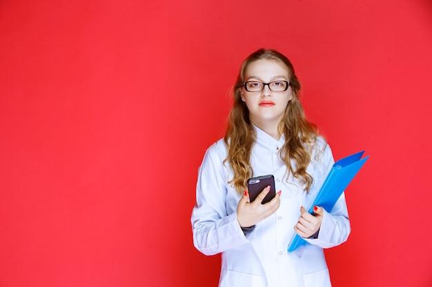 파란색 폴더와 그녀의 전화를 확인하는 안경 의사.