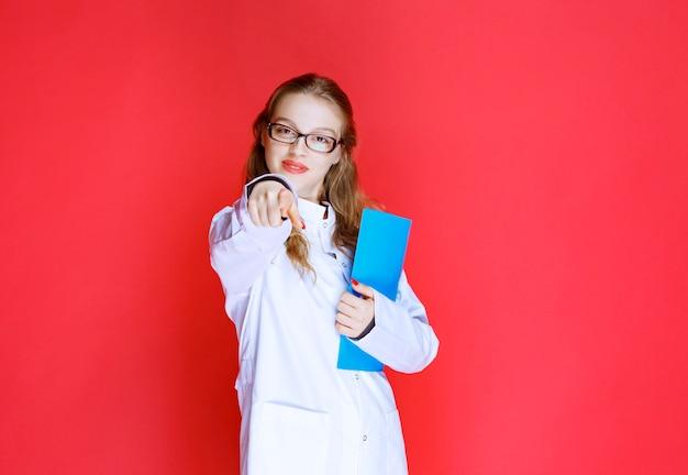 그녀의 환자를 인사하는 파란색 폴더와 의사입니다.