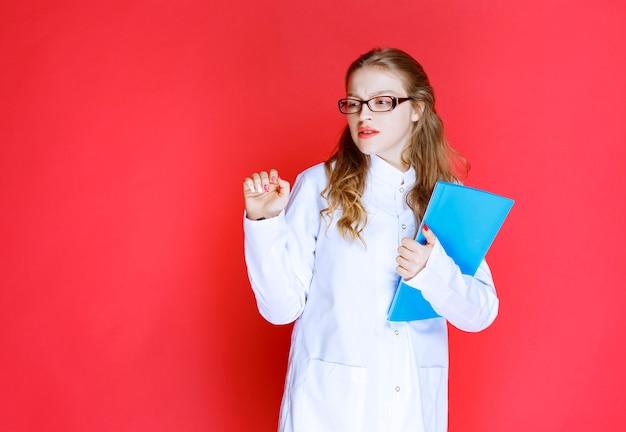 파란색 폴더가있는 의사는 피곤해 보입니다.