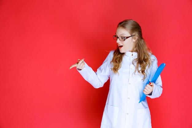 단점을 가리키는 파란색 폴더와 의사.