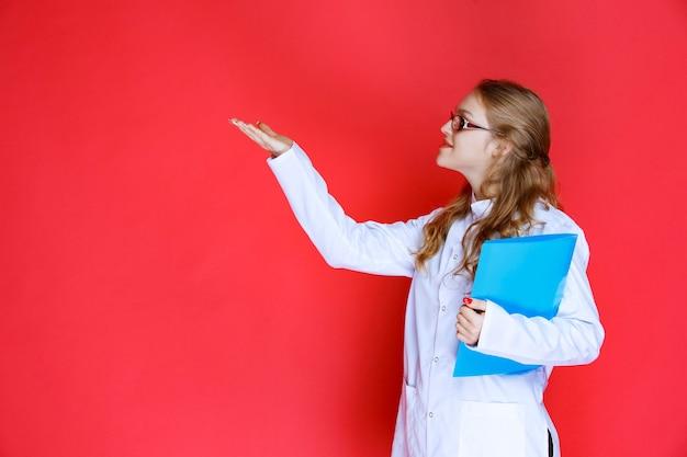 왼쪽을 가리키는 파란색 폴더가있는 의사.