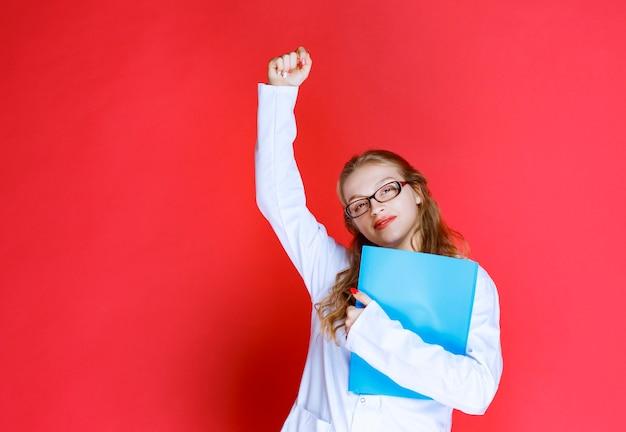 성공적인 손 기호를 보여주는 파란색 폴더와 의사.