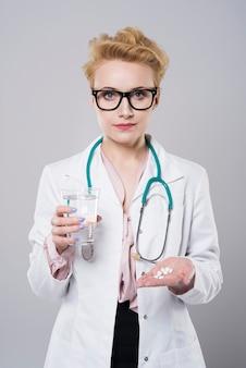 一握りの丸薬を持った医者