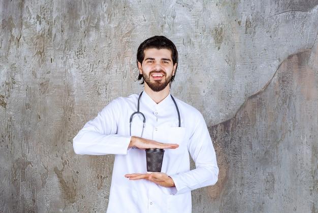黒い使い捨ての飲み物を持っている聴診器を持つ医者。
