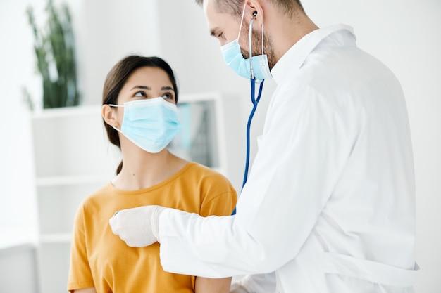 청진기를 가진 의사는 의료 마스크를 착용하는 환자의 심장 박동을 수신합니다