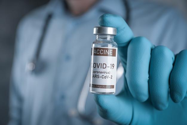 Covid-19、コロナウイルス、sars-cov-2ワクチンを手に持って肩に聴診器を持っている医師。ヘルスケアと医療の概念。開発と作成のワクチン。