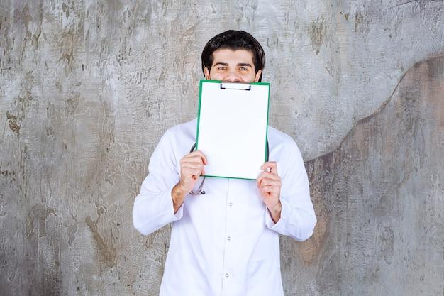 聴診器を持った医師が患者の病歴を示し、顔を後ろに隠している