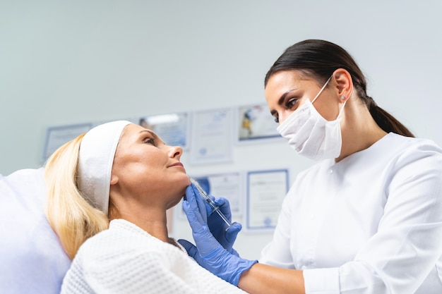 미용 절차 전에 환자의 얼굴 피부를 검사하는 그녀의 손에 주사기를 든 의사