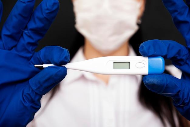 Доктор с термометром. коронавирус. измерение температуры тела. электронный термометр для измерения температуры тела.