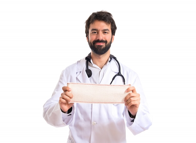 Doctor with bandage over white background