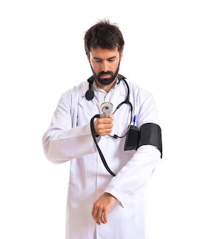 Doctor with blood pressure monitor over white background