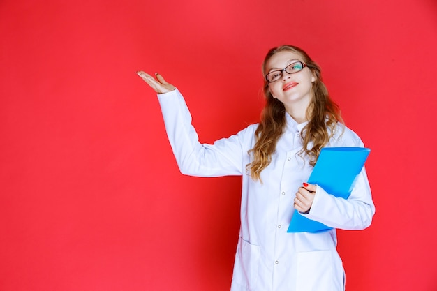 Doctor with a blue folder pointing to the left.