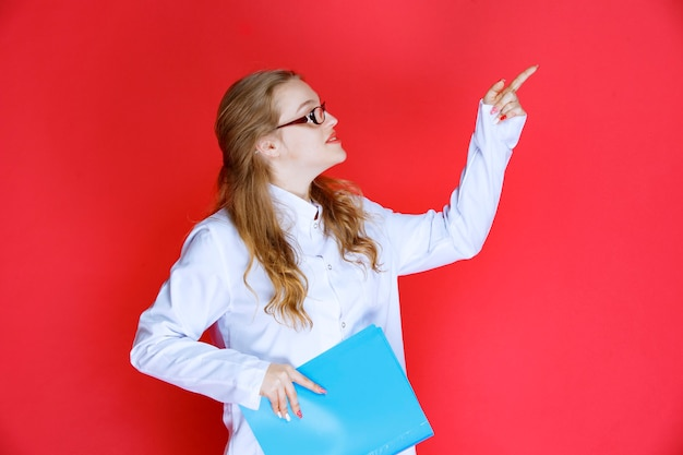 Doctor with a blue folder pointing to the right.