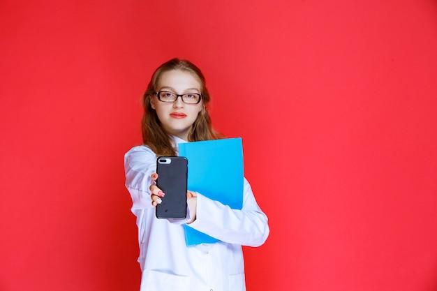 Dottore con una cartella blu che mostra il suo telefono.