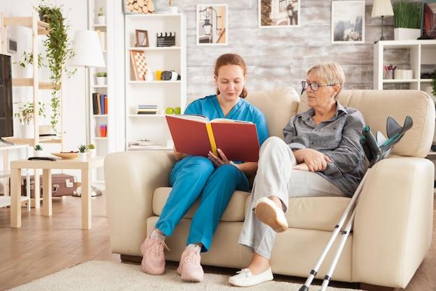 파란색 유니폼을 입은 의사가 은퇴자 집에 있는 고위 여성을 위해 책을 읽고 있습니다.