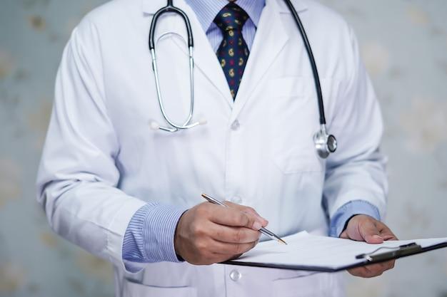 入院中の患者のメモ診断のためのクリップボードを持つ医師。