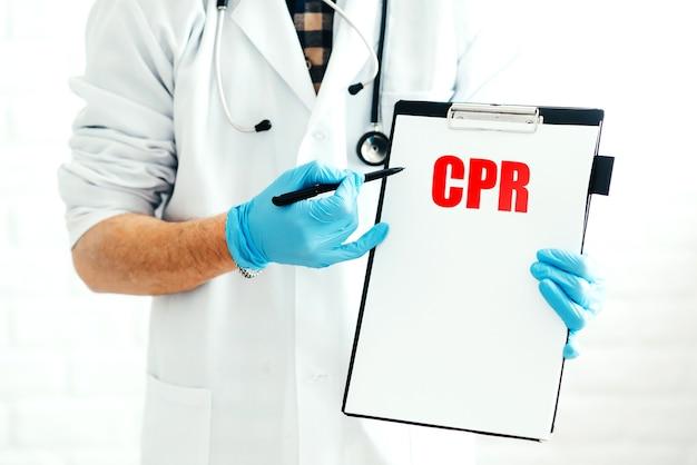Врач с буфером обмена на белом фоне с ручкой показывает название болезни cpr написано красным