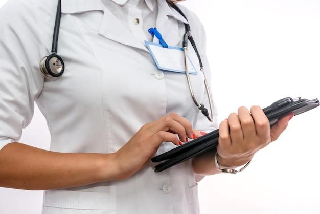 クリップボードを持つ医師。白で隔離されるクリップボードを保持している医療の制服を着たきれいな女性