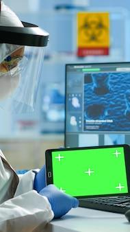 현대적인 시설을 갖춘 실험실에서 녹색 화면이 있는 태블릿에서 작업복을 입은 의사. 크로마 키, 격리된 모형 디스플레이가 있는 장치에서 백신 연구를 하는 미생물학자 팀.
