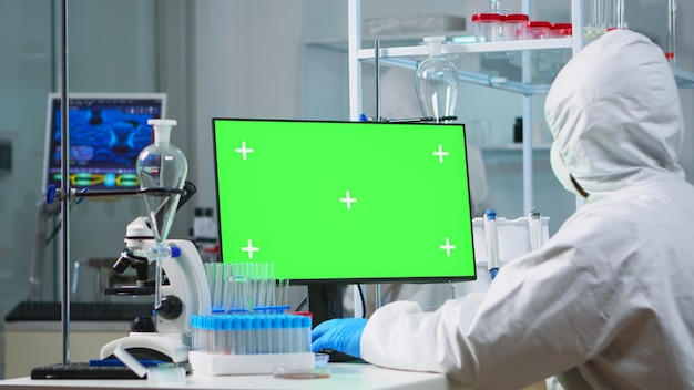 Doctor with coverall working at computer with green screen in modern equipped lab. team of microbiologists doing vaccine research writing on device with chroma key, isolated, mockup display.
