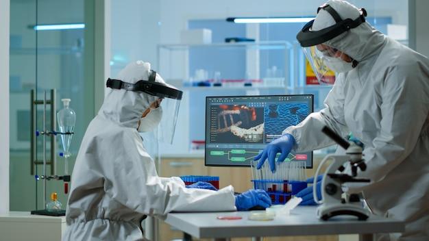 Pc에 입력하는 실험실에서 혈액 샘플을 작업하는 작업복을 입은 의사. covid19 바이러스에 대한 치료 개발 연구를 위해 첨단 기술을 사용하여 백신 진화를 조사하는 화학자 팀