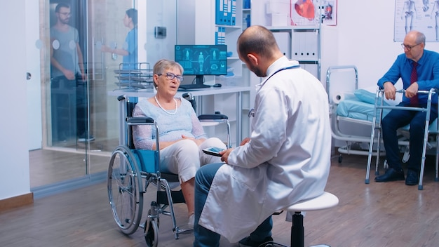 디지털 태블릿을 가진 의사는 노인들을 위한 회복 클리닉에서 의료 조언을 제공합니다. 휠체어를 탄 늙은 은퇴한 여성과 의료 조언과 치료를 구하는 보행 프레임을 가진 남자