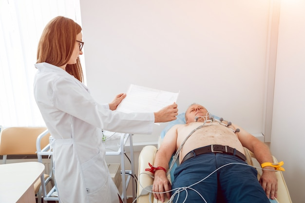 Doctor with electrocardiogram equipment making cardiogram test to patient in clinic.