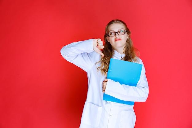 안경 및 파란색 폴더 아래로 엄지 손가락을 보여주는 의사.