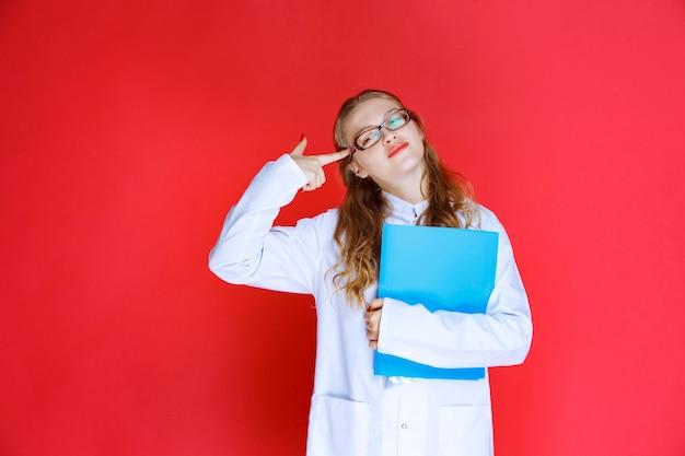 青いフォルダーを保持し、疲れているように見える眼鏡をかけた医師。 無料写真