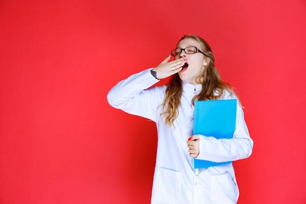 파란색 폴더를 들고 안경 의사와 피곤해 보인다.
