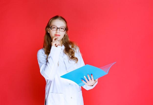 흐림 폴더를 들고 안경 의사입니다.
