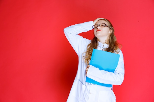 Doctor with eyeglasses holding a blue folder and looks tired.
