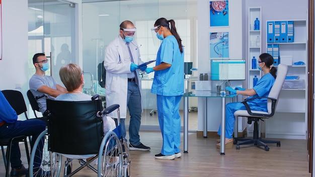 병원 대기실에서 간호사와 논의하는 covid19에 대한 얼굴 마스크를 쓴 의사. 휠체어를 탄 장애인 노인 여성이 검사를 기다리고 있습니다. 리셉션 컴퓨터에서 작업하는 어시스턴트.