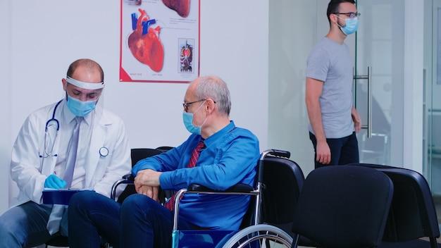 Доктор с лицевой маской и стетоскопом консультирует старшего инвалида в зоне ожидания больницы. медицинский персонал носит защиту от заражения коронавирусом. старушка входит в клинику.