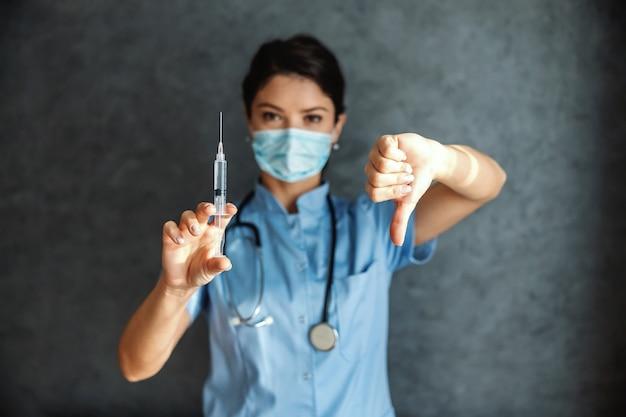 백신과 주사기를 들고 얼굴 마스크와 의사