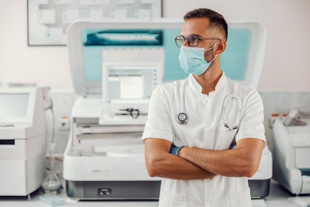 Врач с маской для лица стоит в больнице во время вспышки вируса короны.