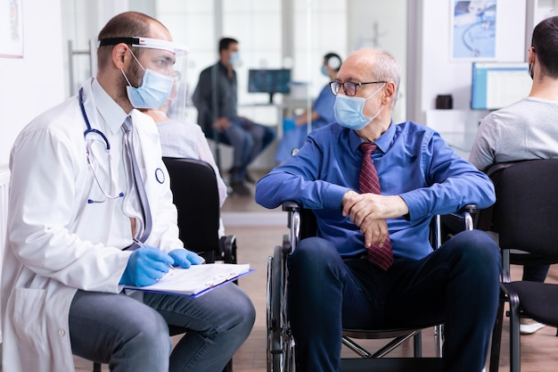 Doctor with face mask and stethoscope consulting disabled senior man in hospital waiting area
