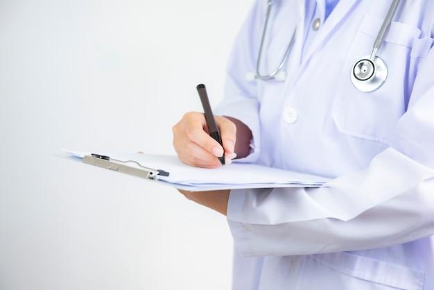 ファイルとクリップボードを押しながら処方箋を書く病院の廊下に聴診器を持つ医師